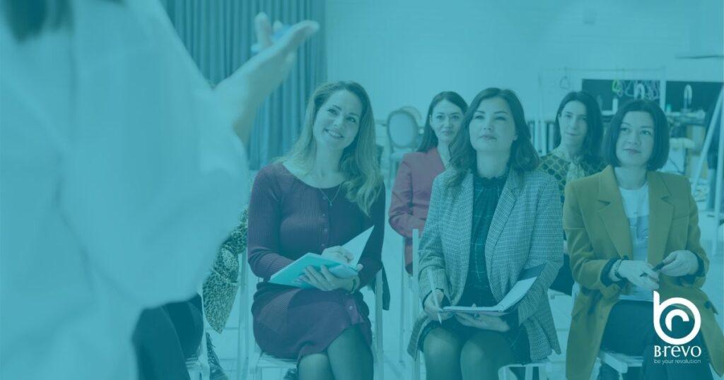 Gruppo di donne sedute tra il pubblico per la formazione aziendale