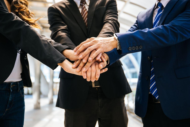 Team di colleghi di lavoro si unisce per sostenersi tenendosi per mano