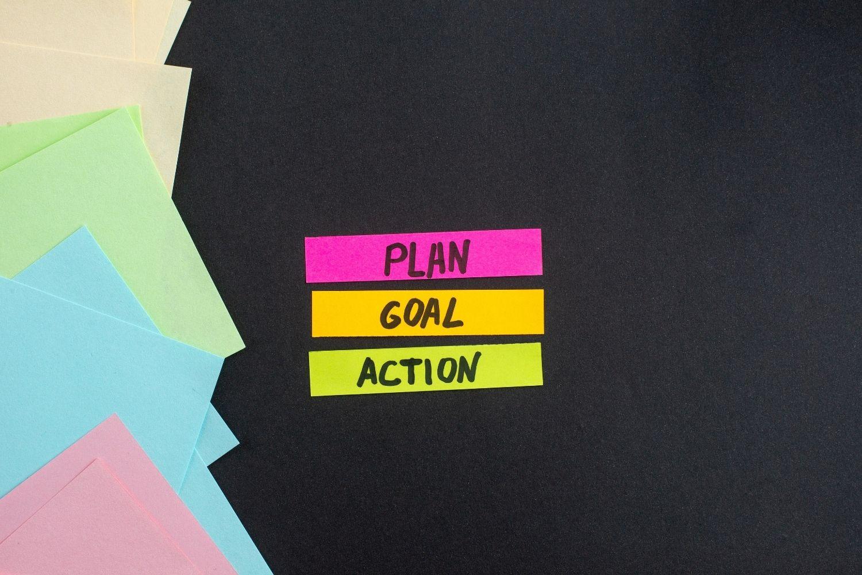 Vista dall'alto delle note pianifica - obiettivo - azione su sfondo scuro