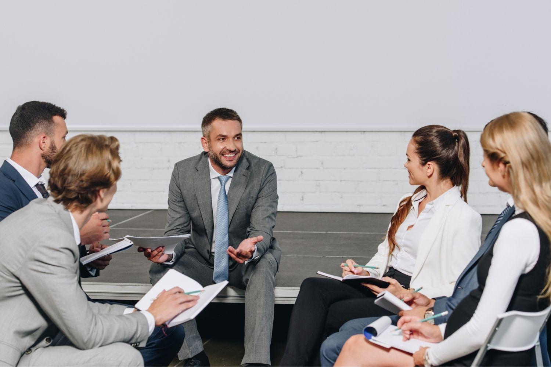 business coach che osserva persone di un team durante una sessione di team coaching